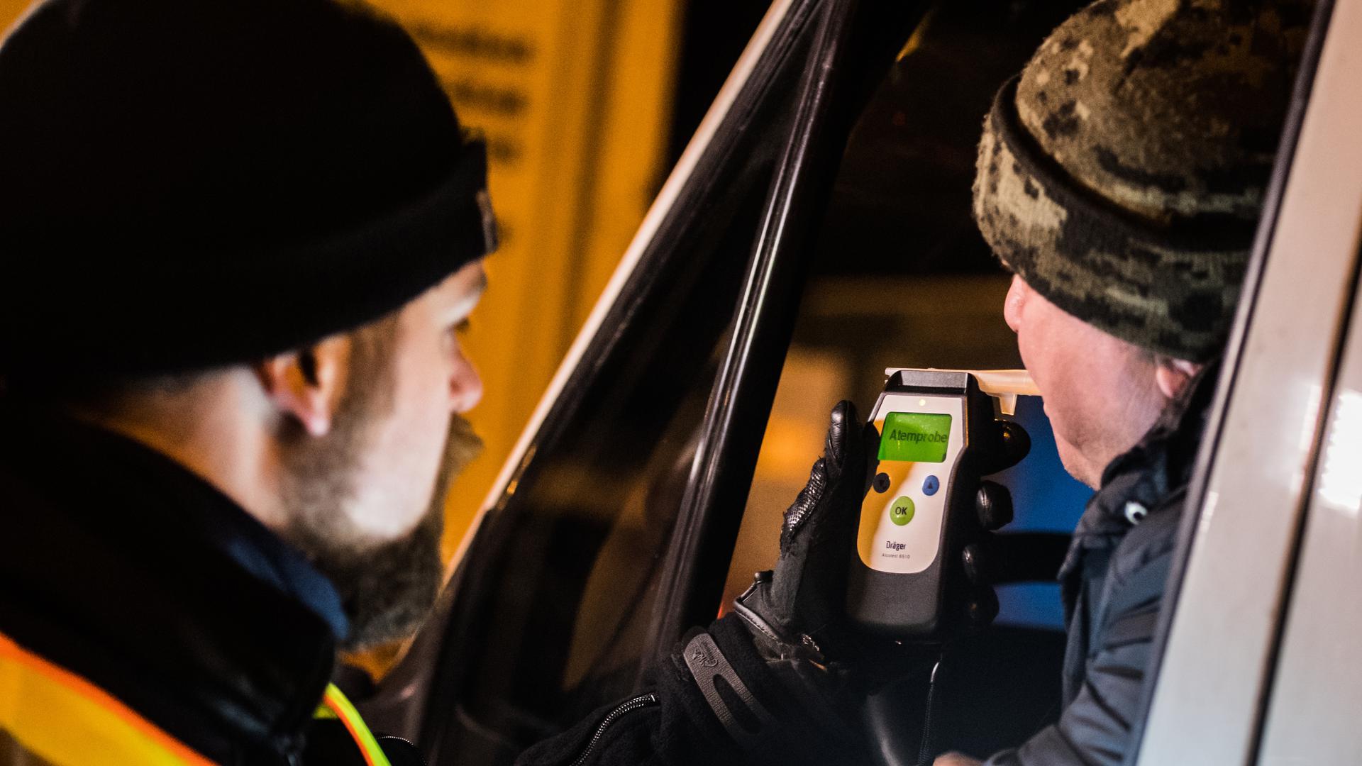 Ein Polizist kontrolliert einen LKW-Fahrer auf Alkoholgenuss. Rund ein Jahr nach ersten großangelegten Kontrollen von Lastwagenfahrern sieht die Polizei Erfolge im Kampf gegen Alkohol am Steuer. +++ dpa-Bildfunk +++