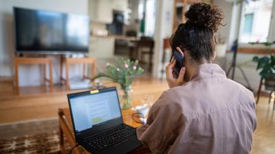 Eine Frau sitzt zu Hause vor dem Laptop
