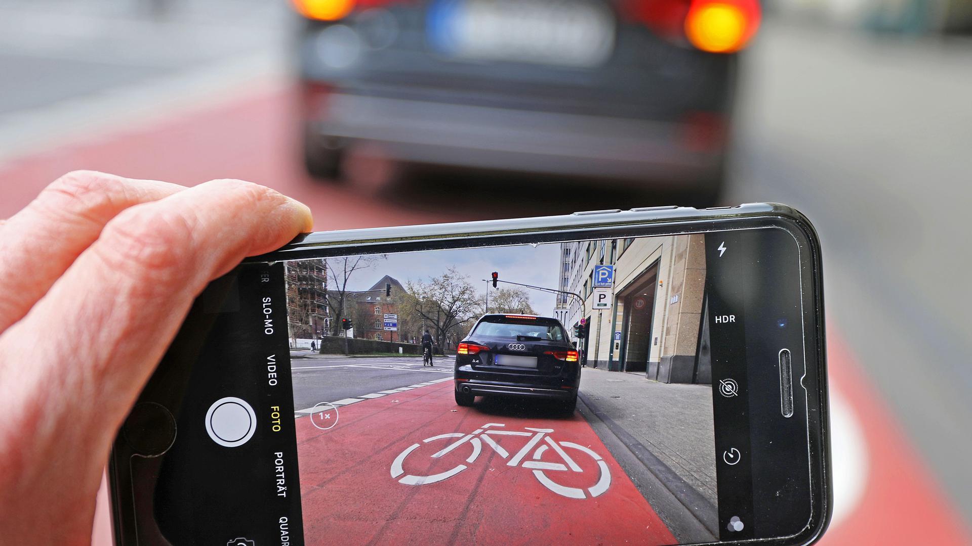 """ILLUSTRATION - Auf einem Smartphone ist das Bild eines Autos zu sehen, das auf einem Radstreifen hält. Eine wachsende Zahl von Parksünden wird in Nordrhein-Westfalens großen Städten von Privatleuten gemeldet. (Zu dpa: """"Privatleute gegen Parksünder: Zahl von Fremdanzeigen gestiegen"""") +++ dpa-Bildfunk +++"""