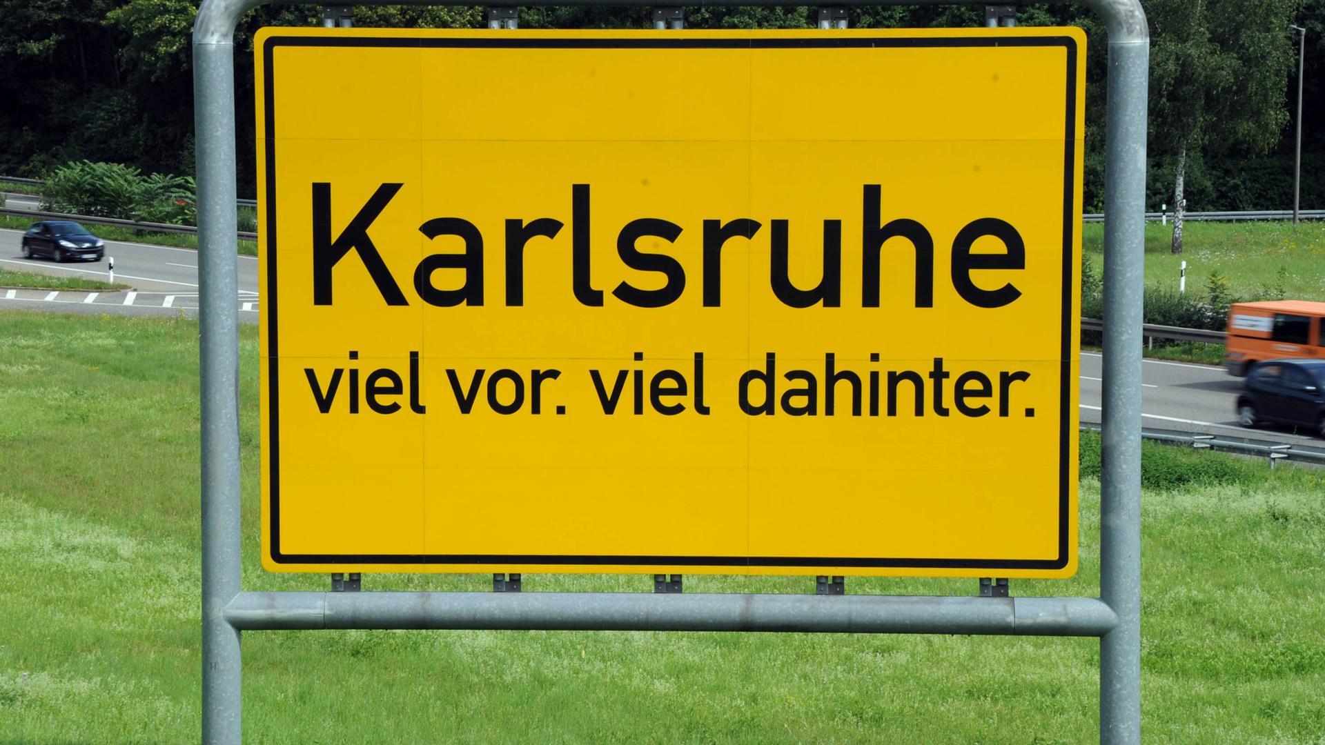 An der Karlsruher Südtangente steht ein überdimensionales Ortsschild auf dem der Karlsruher Werbeslogan steht «Karlsruhe viel vor. viel dahinter.»