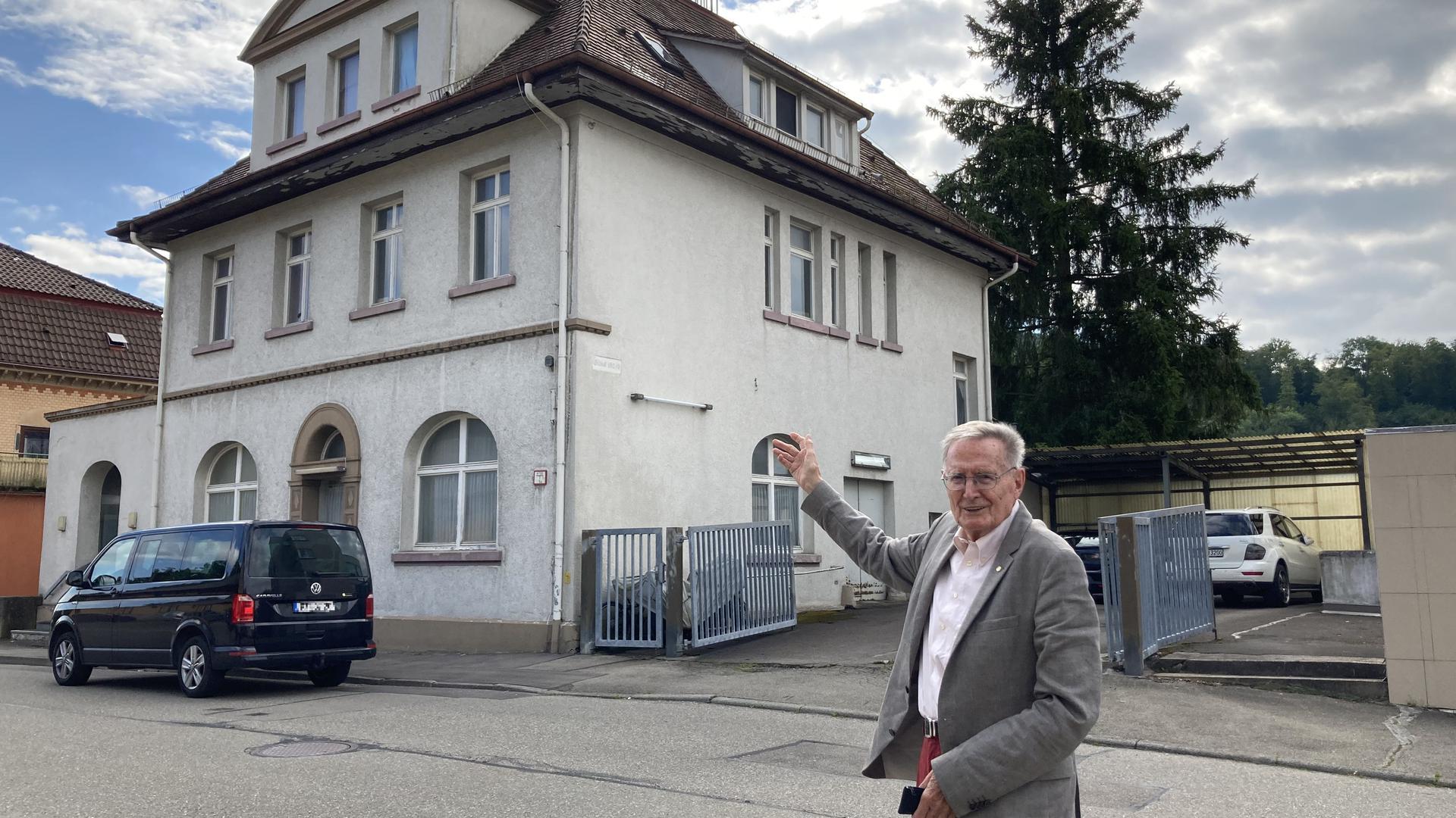 Mann steht vor einem Haus