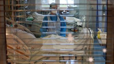 Eine Pflegekraft steht im Infektionszimmer für Covid-19-Patienten.