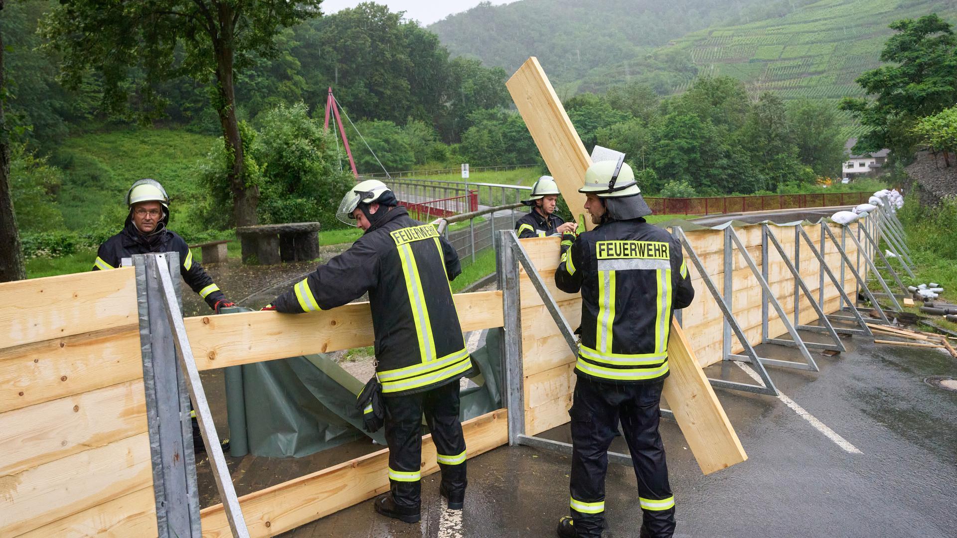 Feuerwehrleute errichten im Ahrtal bei Mayschoss eine Sperrwand aus Holz. Sie soll verhindern, dass das Hochwasser der Ahr in den Ort läuft.