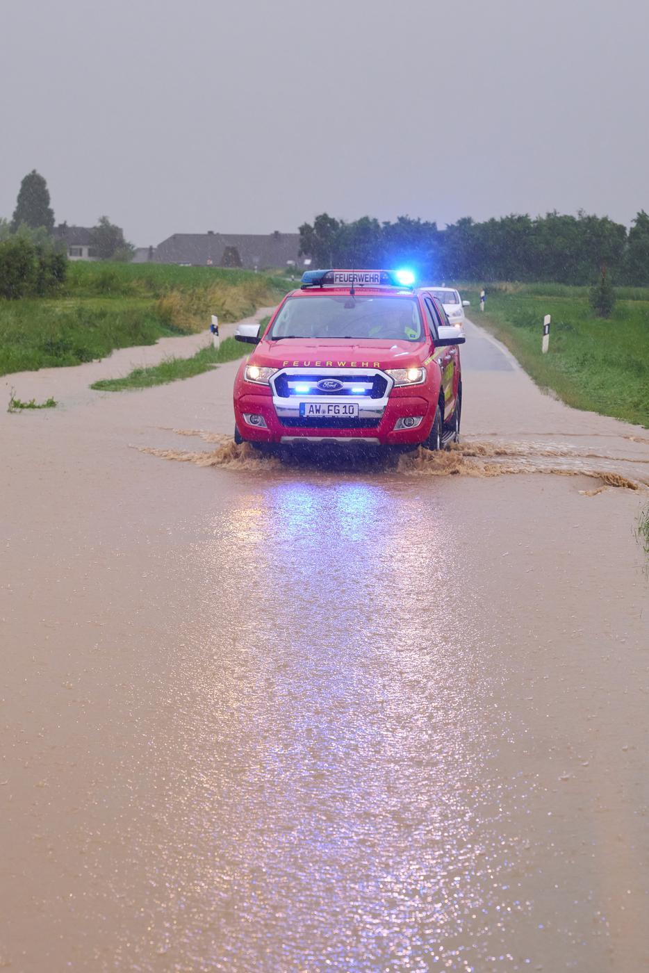 Ein Feuerwehrauto fährt bei Gelsdorf (Kreis Ahrweiler) über eine überflutete Landstrasse. Tief Bernd bringt Regen über Eifel und Hunsrück, die Hochwassergefahr steigt.