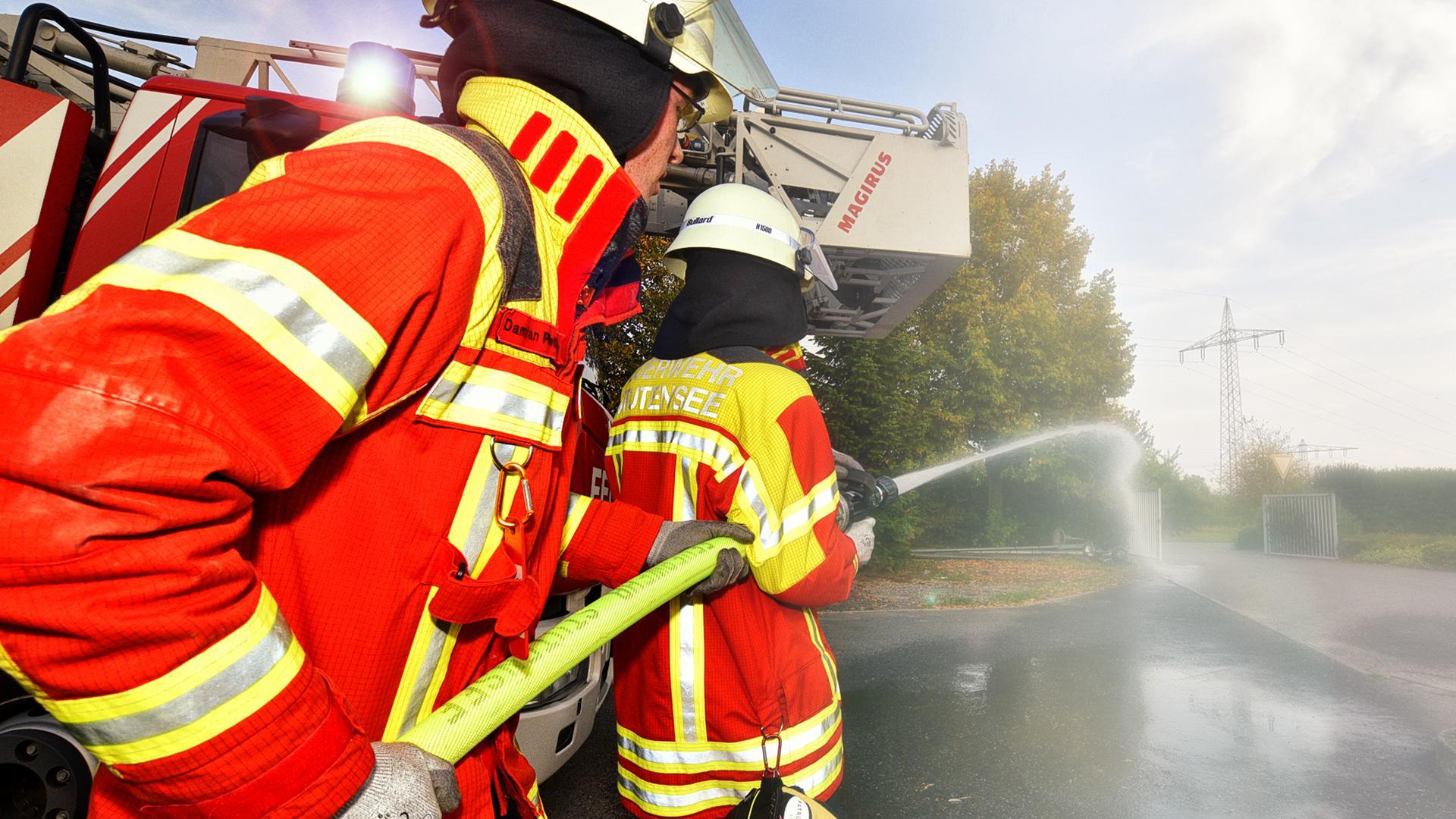 Mitglieder der Feuerwehr halten einen Wasserschlauch (Symbolbild).