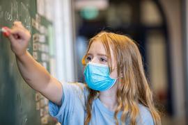 Schülerin mit Maske an Tafel