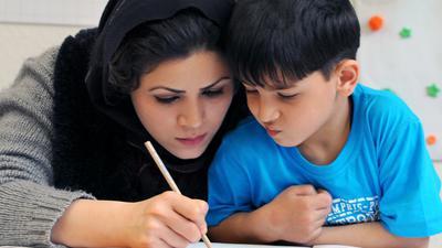 """In einem Integrationskurs """"Deutsch als Fremdsprache"""" an der Volkshochschule Leipzig schreibt Kobra Soltani aus Afghanistan mit ihrem 5-jährigen Sohn Masoud, aufgenommen am 04.04.2011. Der vom Bundesamt für Migration und Flüchtlinge (BAMF) geförderte Kurs gehört zu drei Leistungsstufen mit insgesamt 645 Stunden, die von den ausländischen Teilnehmern innerhalb eines Jahres absolviert werden können. Foto: Waltraud Grubitzsch dpa/lsn  +++(c) dpa - Bildfunk+++"""