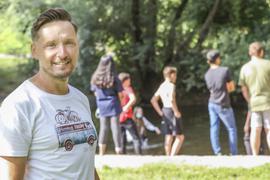 Mann steht im Freien, junge Menschen im Hintergrund