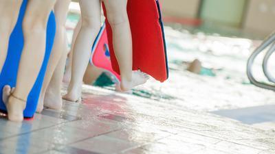 Kinder mit Schwimmhilfen am Beckenrand eines Hallenbades.