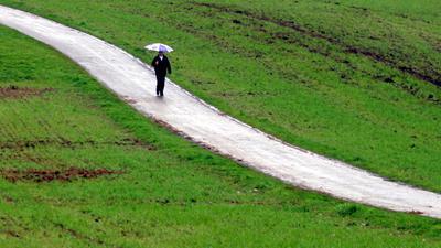 Ein Mann läuft am Sonntag (24.04.2005) bei Löffingen (Landkreis Breisgau-Hochschwarzwald) mit einem Regenschirm auf einem Feldweg durch grüne Felder. Bis zur Wochenmitte soll es nach Angaben der Meteorologen in Baden-Württemberg weiter wechselhaft mit Schauern bleiben. Foto: Patrick Seeger dpa/lsw +++(c) dpa - Bildfunk+++