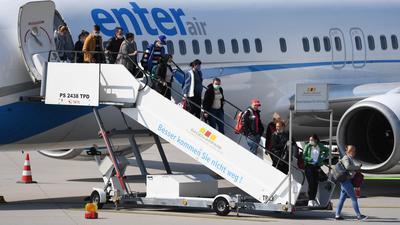 Auf dem Flughafen Karlsruhe/Baden-Baden gehen Erntehelfer, die aus Rumänien eingeflogen wurden, aus einem Flugzeug. Die Erzeuger von Gemüse und Obst, aktuell vor allem die Spargel- und Erdbeeranbauern, sind dringend auf Helfer angewiesen. Wegen der Coronavirus-Pandemie war lange unklar, ob rechtzeitig Arbeiter aus Osteuropa einreisen dürfen. +++ dpa-Bildfunk +++