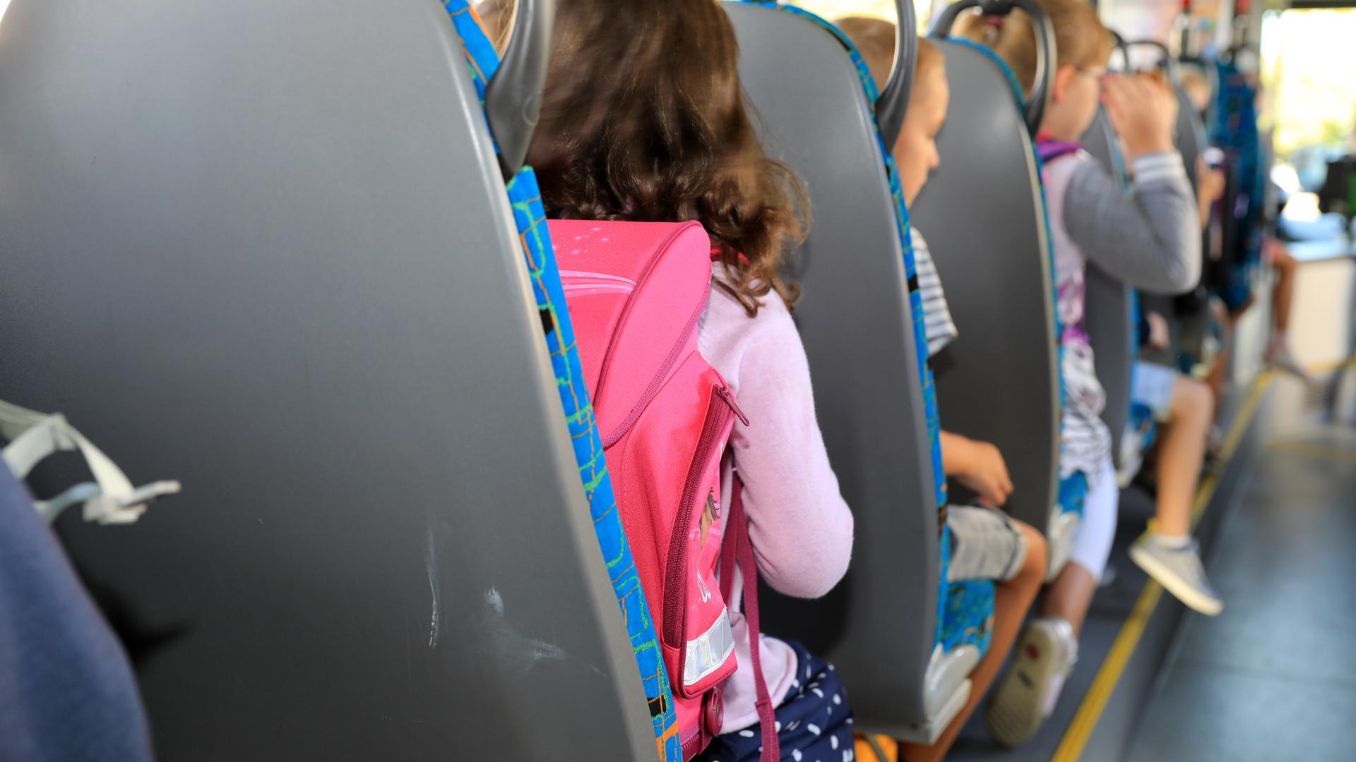 Kinder sitzen mit ihrem Ranzen in einem Schulbus.