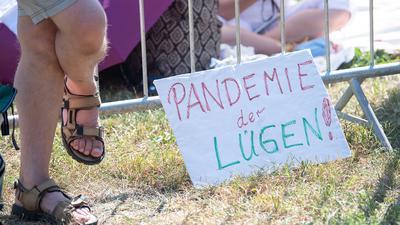 """Ein Schild mit der Aufschrift """"Pandemie der Lügen!"""" steht während einer Kundgebung der Initiative """"Querdenken 711"""" in Stuttgart."""