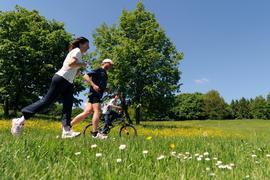 Zwei Jogger und ein Junge auf dem Fahrrad laufen bzw. fahren am Montag (24.05.2010) in München (Oberbayern) in der Nähe des Feldmochinger Sees an einer Wiese vorbei. Nach einen sonnigen Pfingstwochenende soll das Wetter in Bayern ab Dienstag wieder unbeständig und regnerisch werden. Foto: Tobias Hase dpa/lby  +++(c) dpa - Bildfunk+++