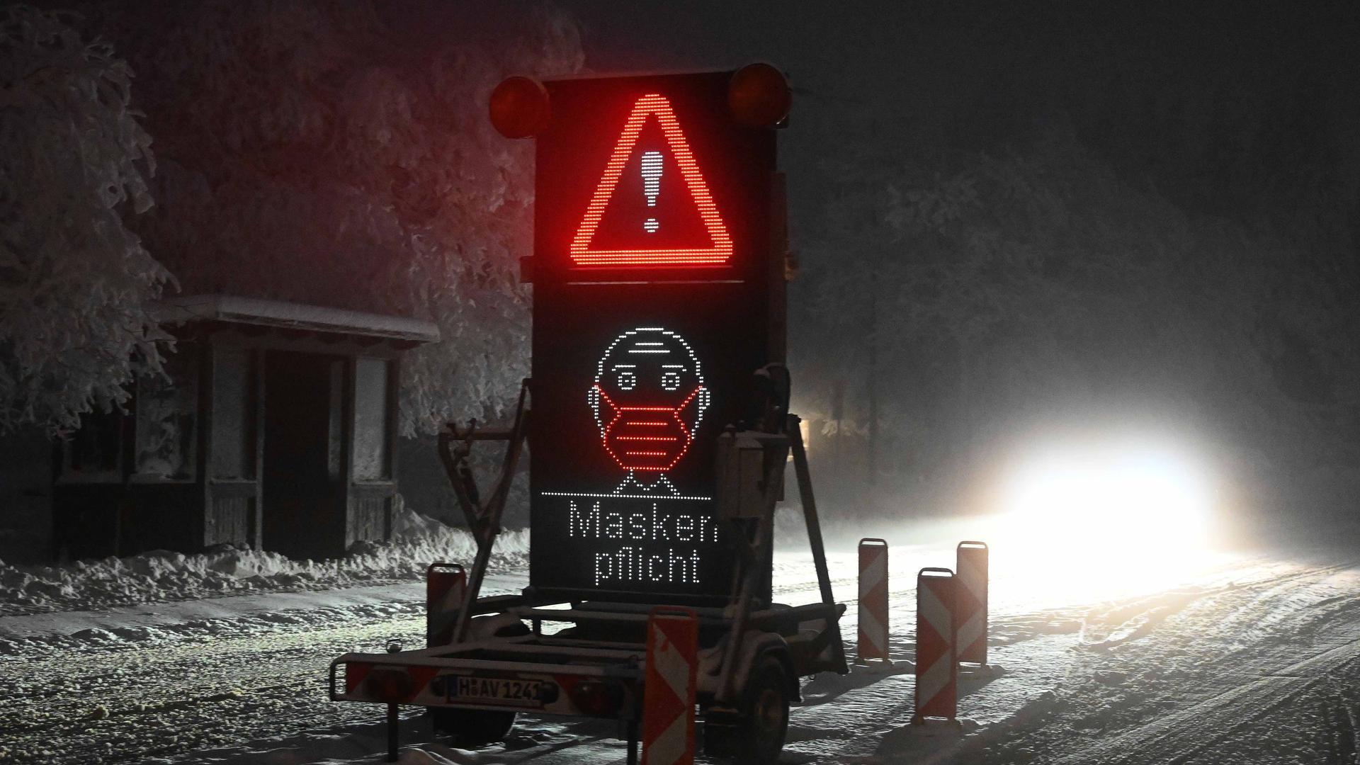 Ein Verkehrsschild mit dem Hinweis «Maskenpflicht» steht auf einer Zufahrt zu einem Parkplatz.