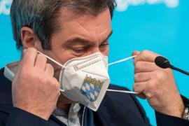 Markus Söder (CSU), Ministerpräsident von Bayern, nimmt sich vor Beginn einer Pressekonferenz eine FFP-2 Maske, die mit dem bayerische Staatswappen auf der Vorderseite bedruckt ist, vom Gesicht ab. Im Mittelpunkt der Beratungen stand einmal mehr die Corona-Pandemie. Seit Anfang dieser Woche gelten in Bayern erneut verschärfte Regeln zur Bekämpfung der Pandemie. Der Lockdown ist zunächst bis zum 31. Januar befristet. +++ dpa-Bildfunk +++