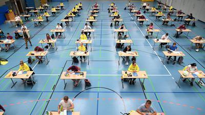 Schüler und Schülerinnen sitzen während der Deutsch-Abitursprüfung mit dem vorgeschriebenen Abstand zueinander in der Sporthalle des Albert-Einstein-Gymnasiums vor ihren Prüfungsaufgaben. (zu dpa «Abschlussprüfungen an Schulen werden wegen Corona-Pandemie angepasst») +++ dpa-Bildfunk +++