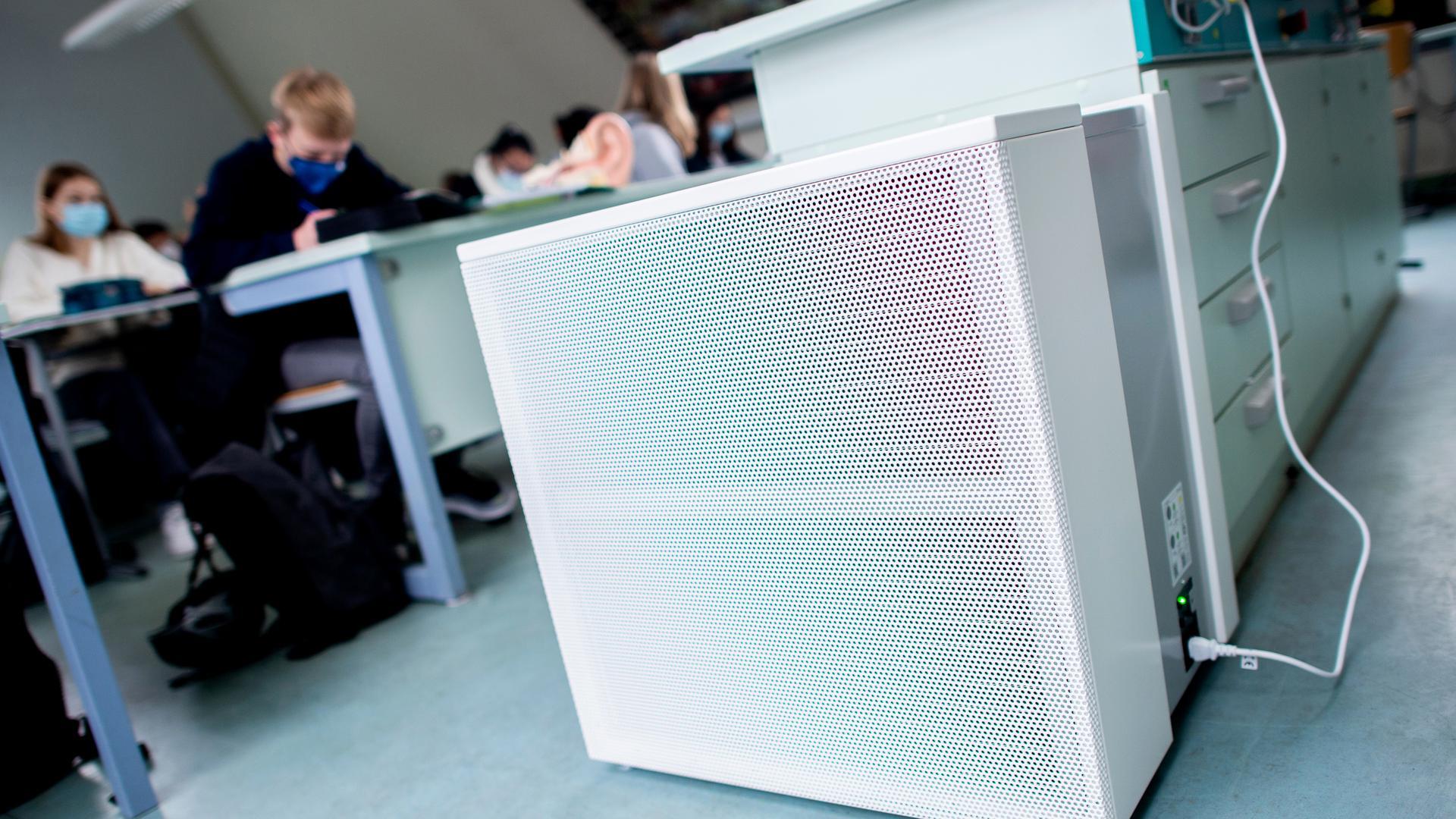 Schüler sitzen in einem Klassenzimmer, im Vordergrund ein Luftfiltergerät.