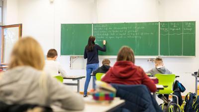 Schülerinnen und Schüler einer fünften Klasse  sitzen während dem Unterricht in ihrem Klassenzimmer.