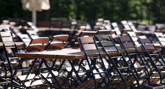 Mehrere Stühle sind in einem geschlossenen Biergarten im Tiergarten an die Tische angelehnt.