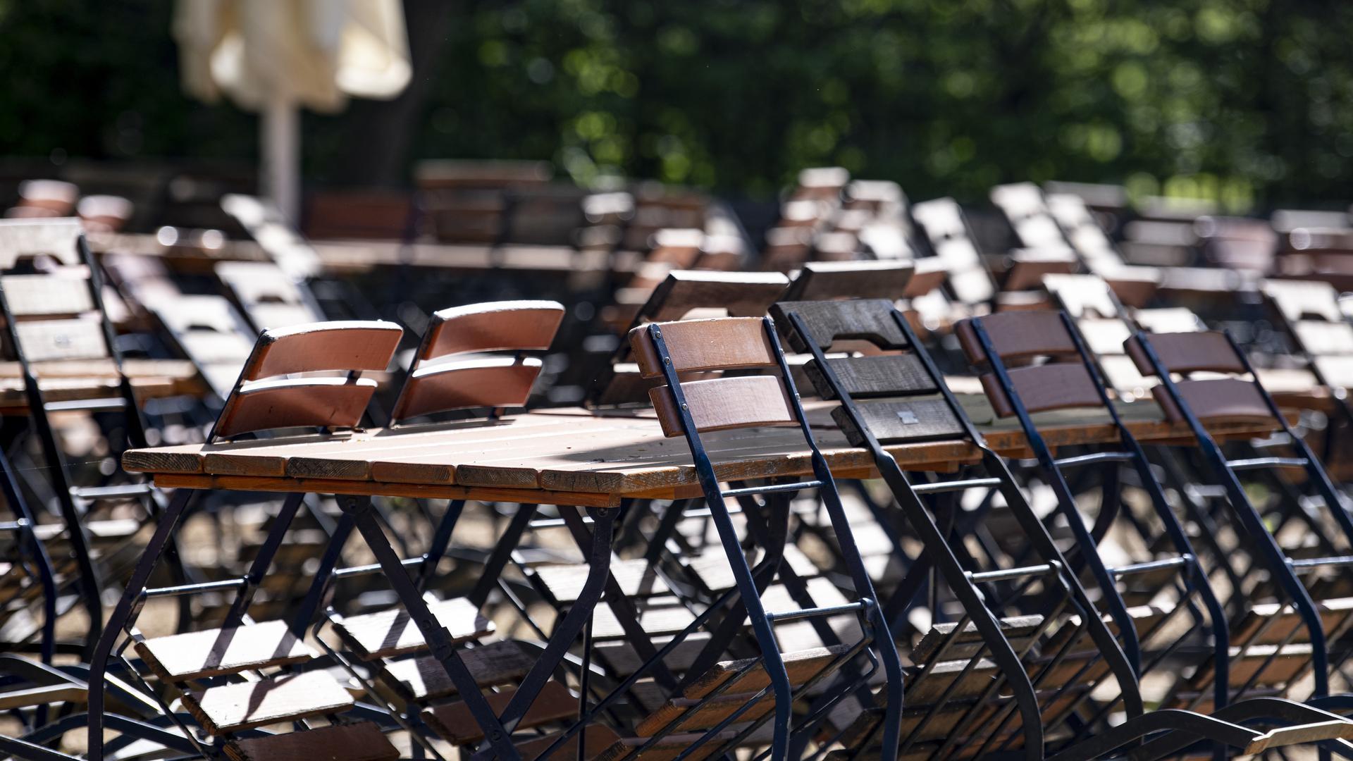 Mehrere Stühle sind während der Corona-Pandemie in einem geschlossenen Biergarten im Tiergarten an die Tische angelehnt.