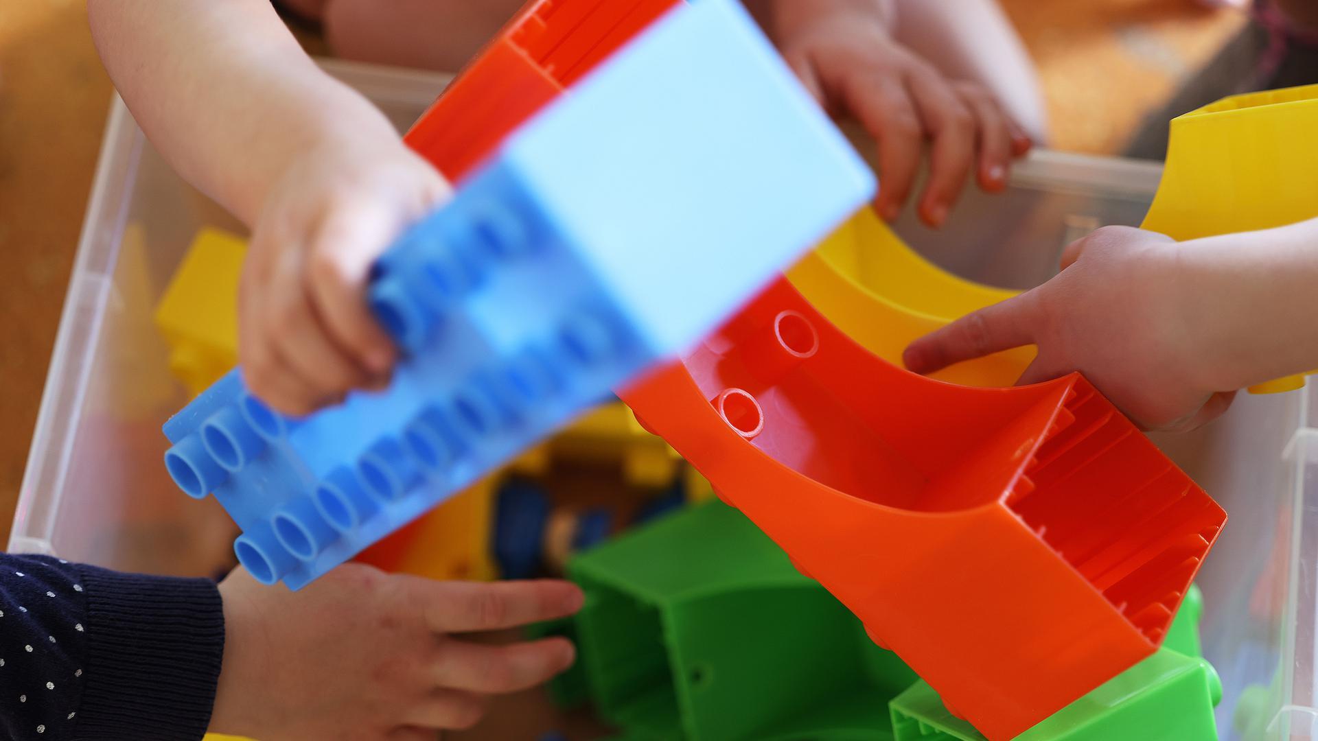 Kinder nehmen in der Kindertagesstätte Kita Morgenland Spielsteine aus einer Kiste. Die Kindertagesbetreuung in Nordrhein-Westfalen kehrt zurück in den Regelbetrieb. +++ dpa-Bildfunk +++