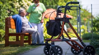 """Ein Rollator steht nahe einer Pflegefachkraft und einer Bewohnerin des Seniorenheims «Mein Zuhause Nienburg» im Freien. Die Corona-Krise hat Seniorenheime hart getroffen. Um pflegebedürftige Menschen zu schützen, brauchte es strenge Regeln. (zu dpa """"Masken wertvoll wie Gold - Wie ein Seniorenheim die Pandemie erlebt"""") +++ dpa-Bildfunk +++"""