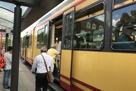 Menschen steigen in einer Straßenbahn des Karlsruher Verkehrsverbundes ein.