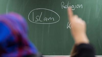 """ARCHIV - ILLUSTRATION - Eine Schülerin mit Kopftuch meldet sich am 05.02.2015 an einer Schule in Frankfurt am Main (Hessen) bei einer Unterrichtsstunde zum Thema Islam. Eine Fachtagung befasst sich am 09.12.2015 in Hannover (Niedersachsen) mit der wachsenden Verbreitung radikal islamischen Gedankenguts an Schulen. Foto: Frank Rumpenhorst/dpa (zu dpa: «Unterricht zum Thema Islam"""" vom 03.06.2016) +++(c) dpa - Bildfunk+++"""