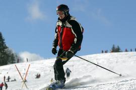 Ein Skifahrer fährt auf einer Piste am Feldberg im Schwarzwald. Sonnenschein und strahlend blauer Himmel bieten hervorragende Bedingungen für eine Skiabfahrt.