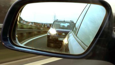 Im Außenspiegel eines Kraftfahrzeugs ist auf der B173 bei Lichtenfels ein dicht auffahrender so genannter Drängler zu sehen (gestellte Aufnahme vom 06.02.2004). Sieben Monate nach dem tragischen Unfalltod einer Mutter und ihrer zweijährigen Tochter bei Karlsruhe beginnt am 9. Februar 2004 der Prozess gegen einen mutmaßlichen Autobahnraser. Der 34-jährige Ingenieur muss sich vor dem Amtsgericht Karlsruhe verantworten. Die Anklage lautet auf fahrlässige Tötung, fahrlässige Gefährdung des Straßenverkehrs und Unfallflucht. Der Fall hatte im Sommer 2003 bundesweit für Aussehen gesorgt. Die Staatsanwaltschaft wirft dem Angeklagten vor, auf der A5 mit 220 bis 250 Stundenkilometern dicht auf den Kleinwagen der 21-jährigen Frau aufgefahren zu sein. Die Frau verlor daraufhin die Kontrolle über den Wagen. Foto: Marcus Führer dpa