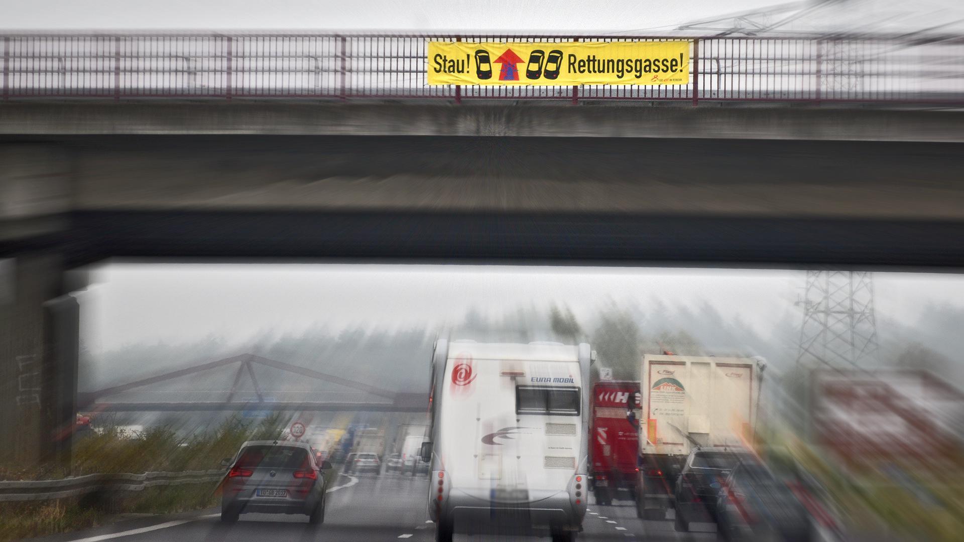 Ein Banner am Geländer einer Autobahnbrücke beschreibt für darunter hindurch fahrende Fahrzeuge die Funktionsweise der Rettungsgasse (Symbolbild)
