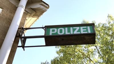 Ein Hinweisschild an der Außenfassade einer Polizeidirektion (Symbolbild)
