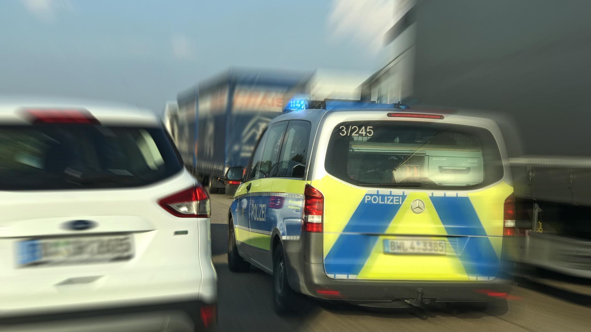 Ein Fahrzeug der Polizei passiert im Einsatz die Rettungsgasse zwischen zwei Fahrbahnen (Symbolbild)