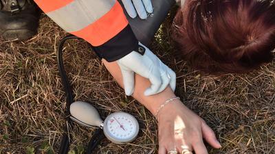 Ein Sanitäter im Einsatz überprüft den Blutdruck einer verunglückten Person (Symbolbild)