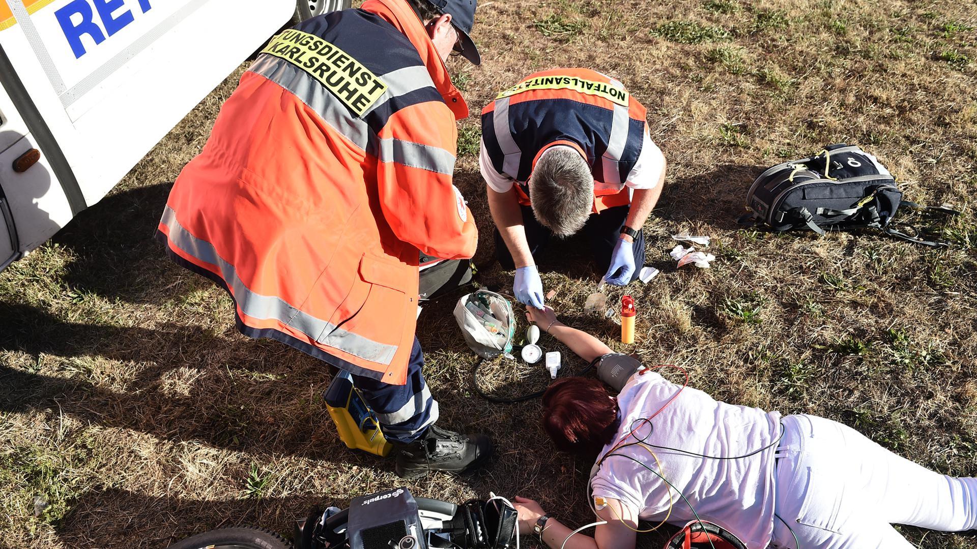 Nach einem Unfall mit einem Fahrrad wird eine verletzte Person von zwei Sanitätern behandelt (Symbolbild)