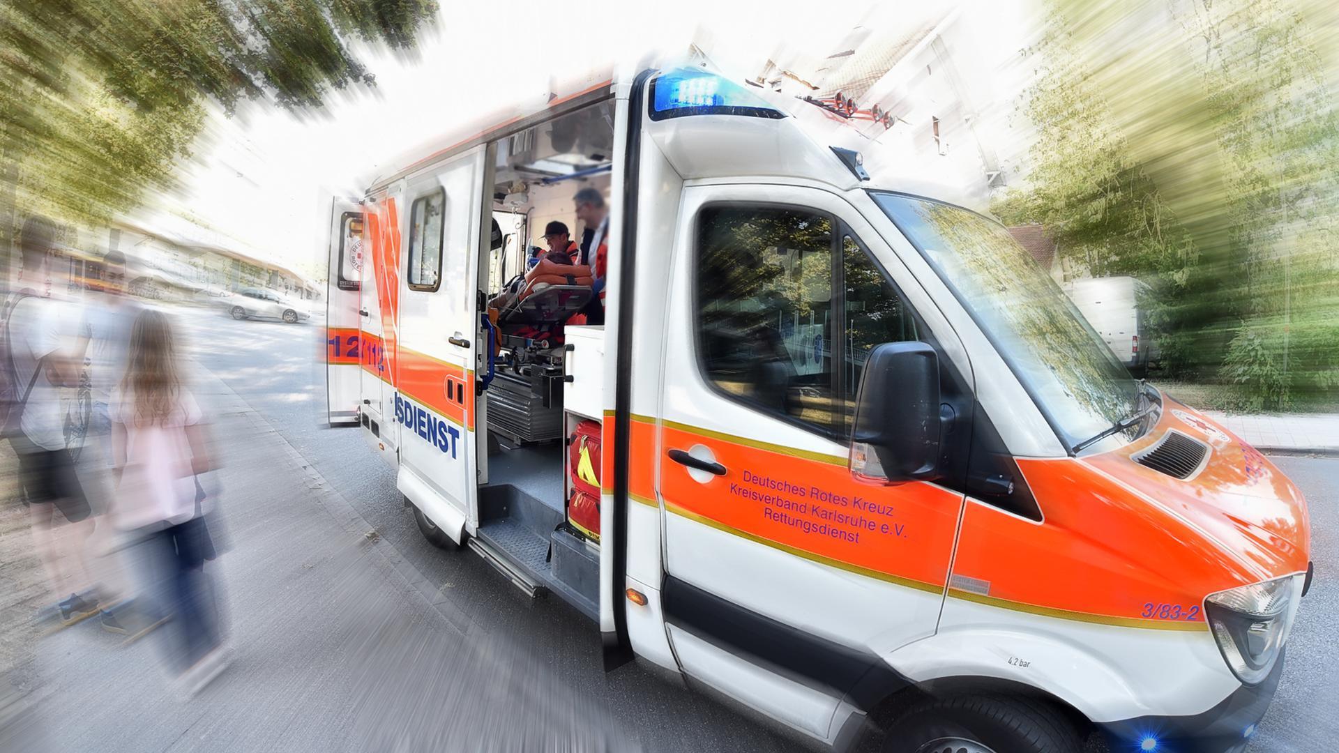Während der Behandlung eines Patienten in einem Krankenwagen versammeln sich mehrere schaulustige Jugendliche davor