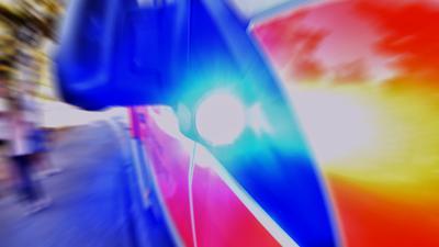 Unter dem Außenspiegel eines Rettungswagen strahlt das signifikante Blaulicht (Symbolbild)