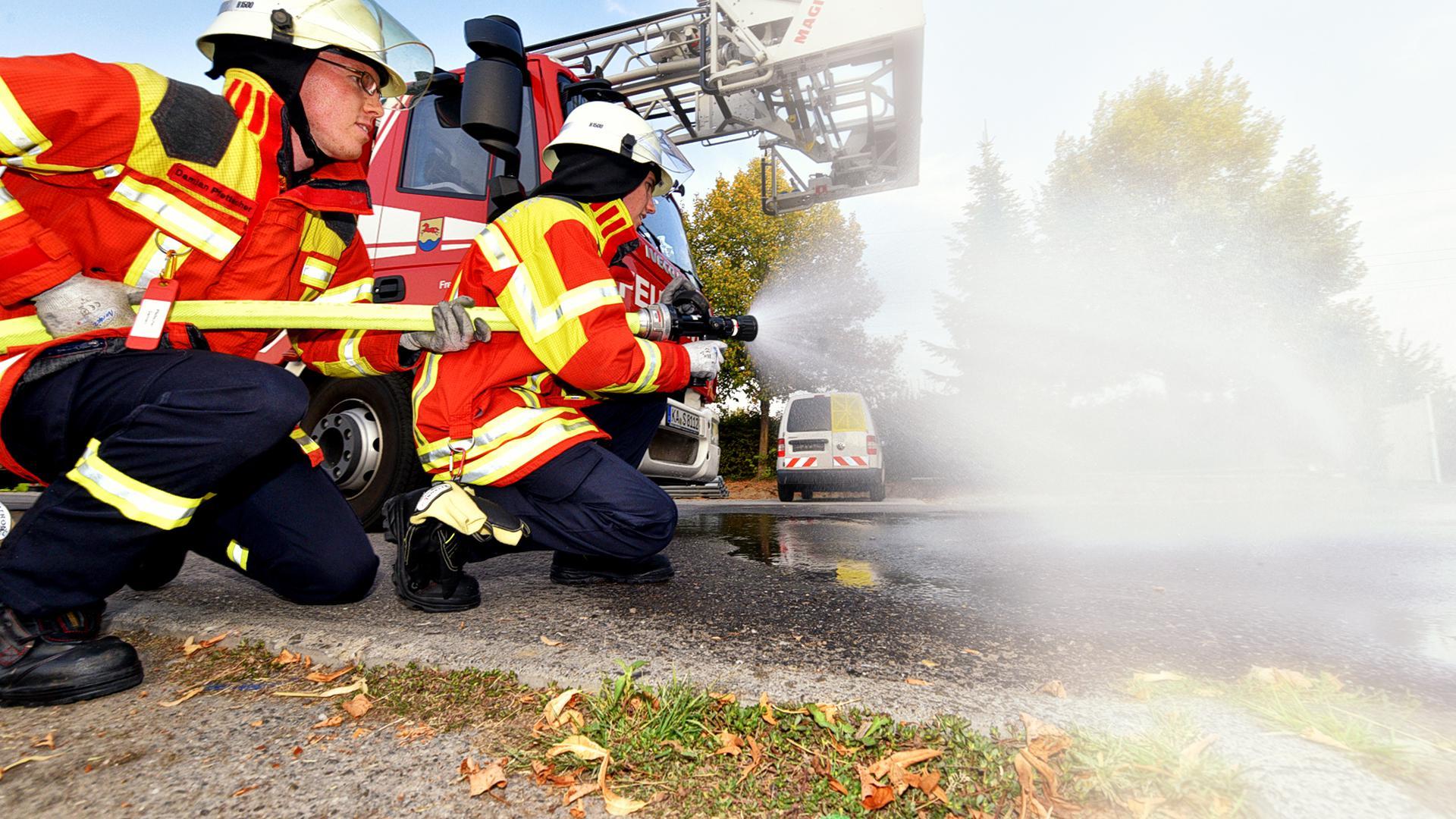 Feuerwehreinsatzkräfte knien vor einem Wagen und halten einen Schlauch (Symbolbild).