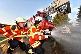 Feuerwehrkräfte knien vor einem Einsatzwagen und halten einen Schlauch (Symbolbild).