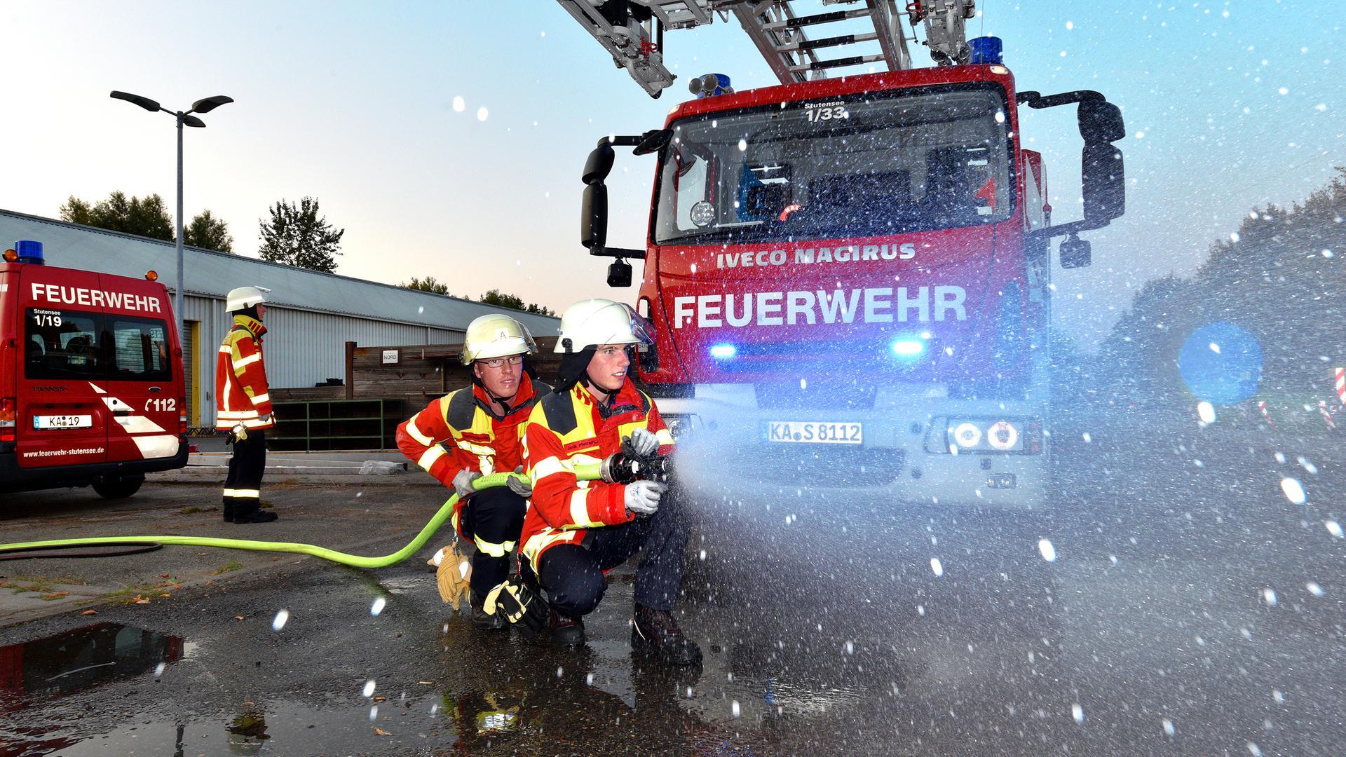 Feuerwehrkräfte halten einen Schlauch vor einem Feuerwehrauto (Symbolbild).