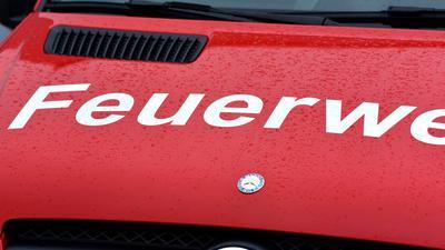 Auf der Motorhaube eines Einsatzwagens steht der Schriftzug Feuerwehr (Symbolbild).