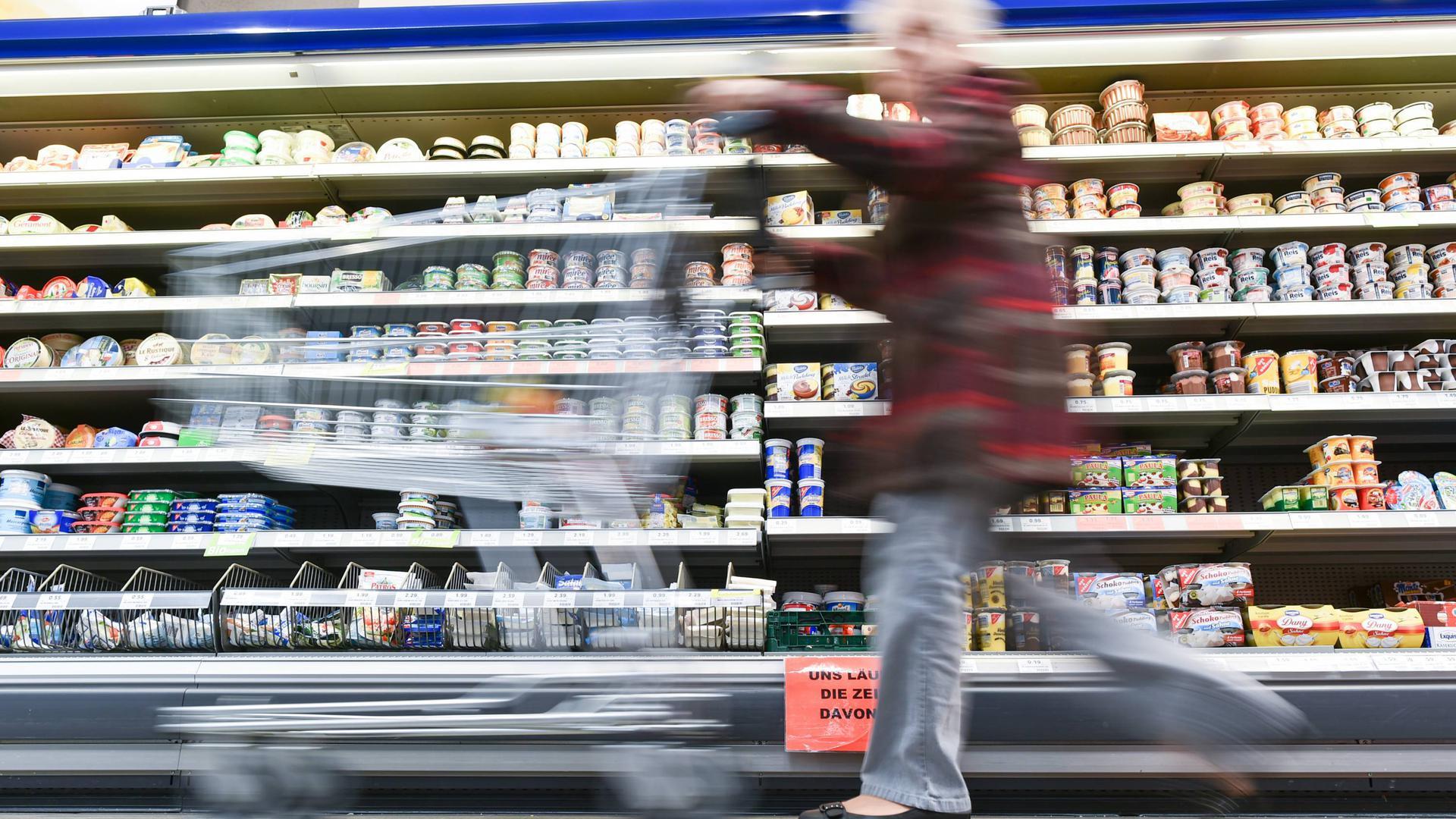 ARCHIV - 09.02.2015, Rheinland-Pfalz, Haßloch: Eine Kundin geht in einem Supermarkt mit ihrem Einkaufswagen an einem Kühlregal vorbei. (zu dpa «Vom Grießbrei bis zu Geschirrspültabs: Viel Ärger mit Verpackungen» vom 17.01.2019) Foto: Uwe Anspach/dpa +++ dpa-Bildfunk +++   Verwendung weltweit