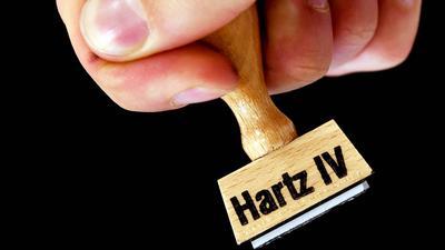 """Eine Hand hält einen Stempel mit der Aufschrift """"Hartz IV""""."""