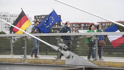 14.06.2020, Frankreich, Straßburg: Mitglieder pro-europäischer französischer und deutscher Verbände gehen mit der deutschen, französischen und europäischen Fahne auf der «Passerelle des Deux-Rives» (Fußgängerbrücke der beiden Ufer), die das französische Straßburg mit dem deutschen Ort Kehl (Baden-Württemberg) verbindet. Die Bundesregierung hebt ab dem 15. Juni für 27 EU-Staaten die Reisewarnung wieder auf, darunter auch für Frankreich. Foto: Jean-Francois Badias/AP/dpa +++ dpa-Bildfunk +++ |