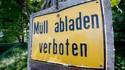 """Ein Schild mit der Aufschrift """"Müll abladen verboten"""" in einem Waldstück."""
