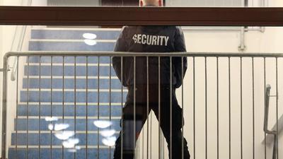 Ein Mitarbeiter einer Security-Firma steht in einem Treppenhaus.