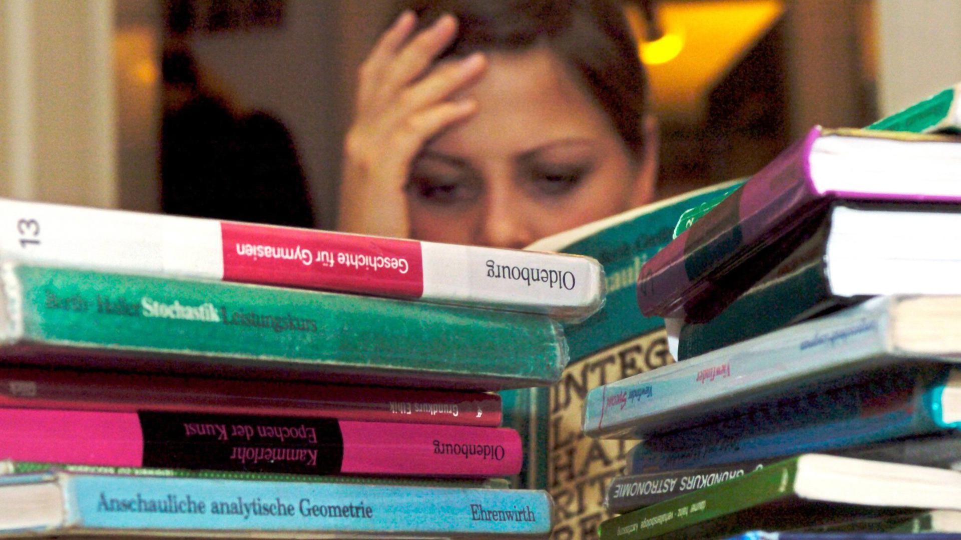 Schülerin sitzt verzweifelt vor Büchern.