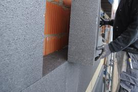 Ein Mann montiert am Donnerstag (04.11.2010) eine Styroporplatte zur Wärmedämmung an die Fassade eines Hauses.