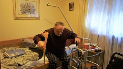 Sergiy Kelm, Rentner aus Iffezheim, sitzt auf seinem Pflegebett und versucht aufzustehen